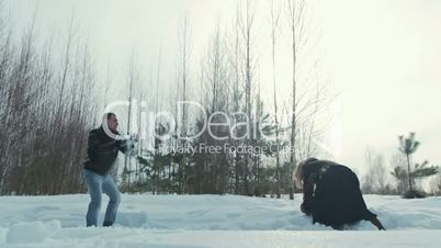 Young couple playing outdoors in the snow, slowmotion