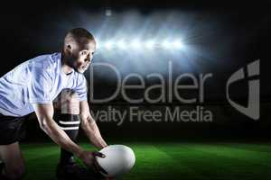 Composite image of rugby player looking away while keeping ball