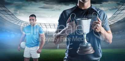 Composite image of victorious rugby player holding trophy