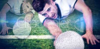 Composite image of man holding rugby ball while lying down