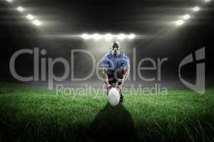 Composite image of portrait of rugby player holding ball while k