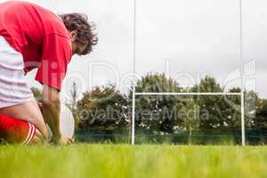 Rugby player getting ready to kick ball
