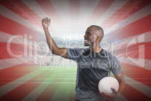 Composite image of sportsman with clenched fist holding rugby ba