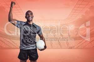 Composite image of happy sportsman with clenched fist holding ru