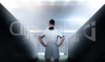 Composite image of rear view of a rugby player with hands on wai