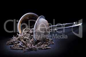 strainer with tea leafs on black