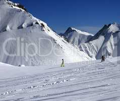 Snowboarders downhill on off piste slope at sun day