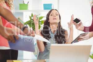 Depressed businesswoman gesturing at desk