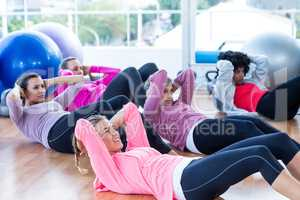 Sporty women doing sit ups on hardwood floor