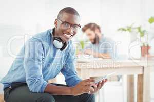 Portrait of smiling man with headphones while using digital tabl