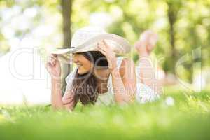 Happy young woman holding sun hat while lying on grassland