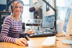 Portrait of female radio host using computer in studio