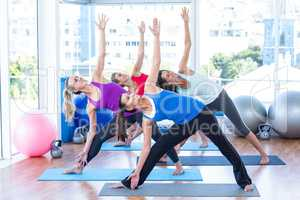 Happy women in fitness studio doing side stretch