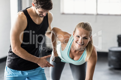 Sporty woman using dumbbells with personal trainor