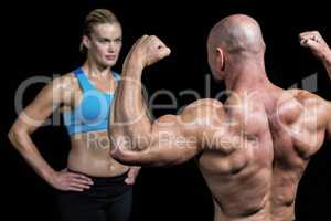 Bald muscular man flexing muscles in front of trainer