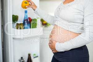 Pregnant woman holding belly pepper from fridge
