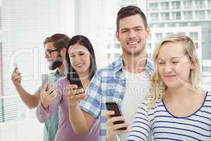 Smiling business professionals using smartphones while standing