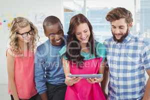 Smiling business professionals using digital tablet