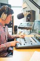 Radio host wearing headphones operating sound mixer