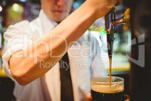 Barkeeper holding beer glass below dispenser tap