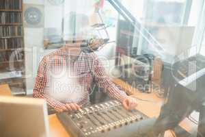 Radio host operating sound mixer in studio