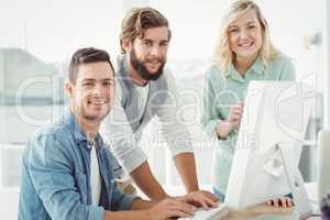 Professionals discussing at computer desk