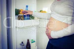 Pregnant woman taking belly pepper from fridge