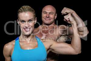 Portrait of confident cheerful man and woman flexing muscles