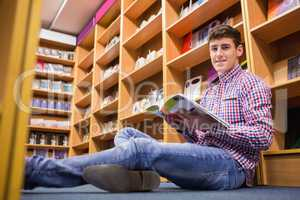 Confident young man with book sitting on flooring
