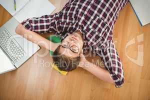Hipster wearing eye glasses lying on hardwood floor