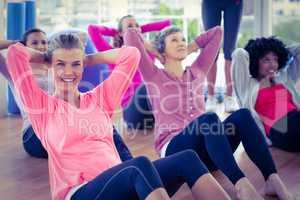 Portrait of woman doing sit ups with friends
