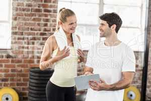 Woman discussing her performance on clipboard with trainer