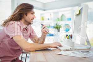 Hipster typing on keyboard while holding electronic cigarette