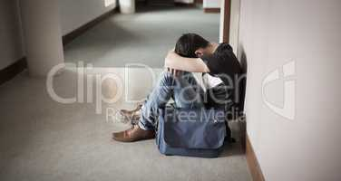 Depressed male student with head on knees
