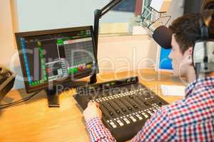Radio host operating sound mixer while looking in monitor