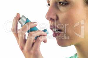 Close-up of woman looking away while using asthma inhaler
