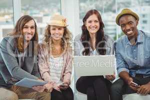 Portrait of smiling business people with laptop and digital tabl