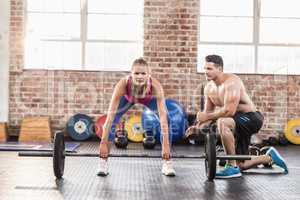 Woman lifting barbell with her trainer at crossfit session