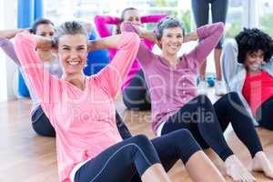 Cheerful women doing sit ups on hardwood floor