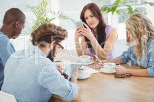 Business professionals using technology while sitting at desk