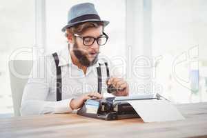 Hipster holding smoking pipe while working on typewriter