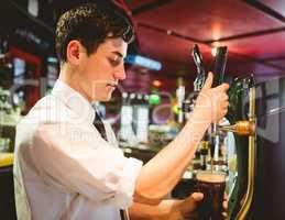 Barkeeper holding beer glass below dispenser tap
