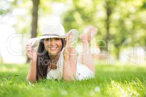 Happy woman holding sun hat while lying on grassland
