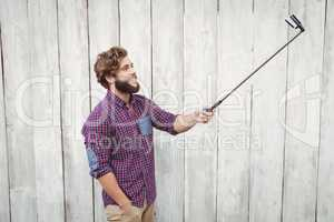 Happy hipster using selfie stick