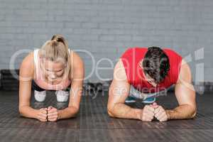 Fit smiling couple planking together in gym