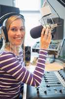 Portrait of happy female radio host broadcasting