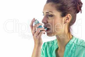 Woman looking away while using asthma inhaler