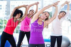 Happy women exercising with arms raised