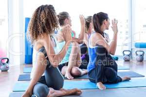 Fit women in fitness studio doing spine twisting pose