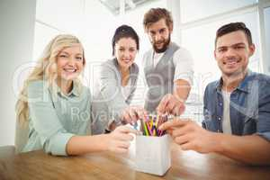 Portrait of smiling business people taking pencils from desk org